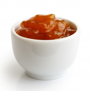 Small ramekin of orange apricot jam isolated on white. In perspective.